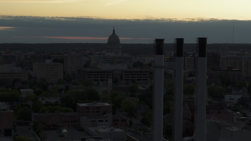 5.7K stock footage aerial video flyby smoke stacks with a view of the capitol dome at sunset, Madison, Wisconsin Aerial Stock Footage | DX0002_162_006
