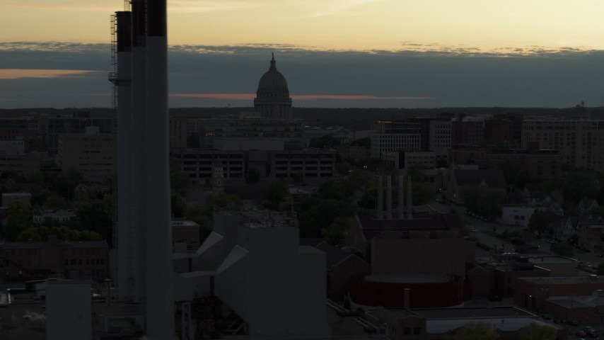 5.7K stock footage aerial video descend and flyby the capitol dome at sunset, reveal smoke stacks Madison, Wisconsin Aerial Stock Footage | DX0002_162_007