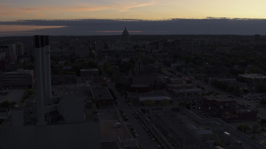 5.7K stock footage aerial video flyby and away from the capitol dome and power plant smoke stacks at twilight, Madison, Wisconsin Aerial Stock Footage | DX0002_162_015