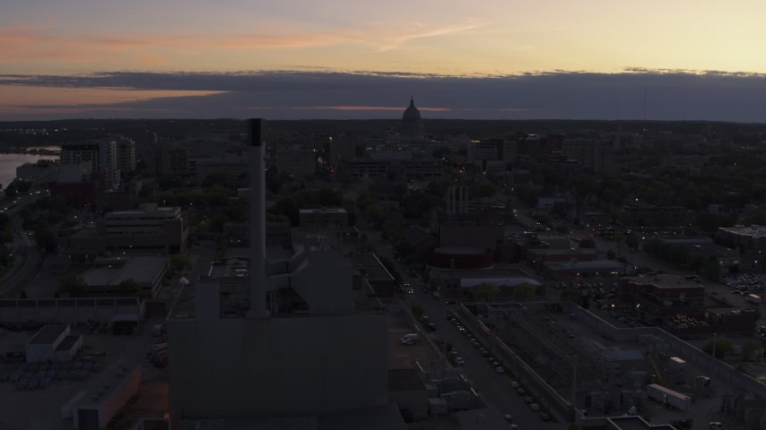 5.7K stock footage aerial video the capitol dome seen while passing power plant smoke stacks at twilight, Madison, Wisconsin Aerial Stock Footage | DX0002_162_017