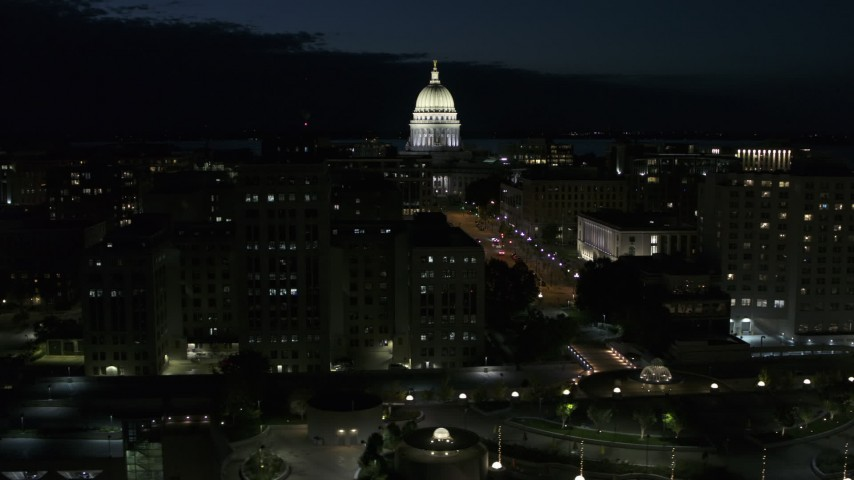 5.7K stock footage aerial video the capitol dome while passing downtown buildings at night, Madison, Wisconsin Aerial Stock Footage | DX0002_162_033