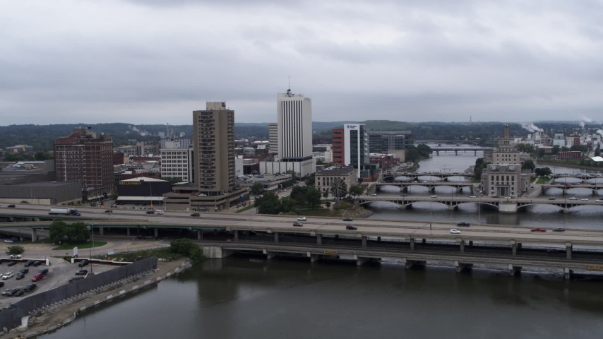 5.7K stock footage aerial video of an apartment high-rise and office buildings near bridges over the river, Downtown Cedar Rapids, Iowa Aerial Stock Footage | DX0002_164_001