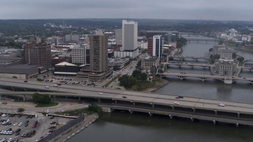 5.7K stock footage aerial video reverse view of apartment high-rise and bridges spanning the river, Downtown Cedar Rapids, Iowa Aerial Stock Footage | DX0002_164_011