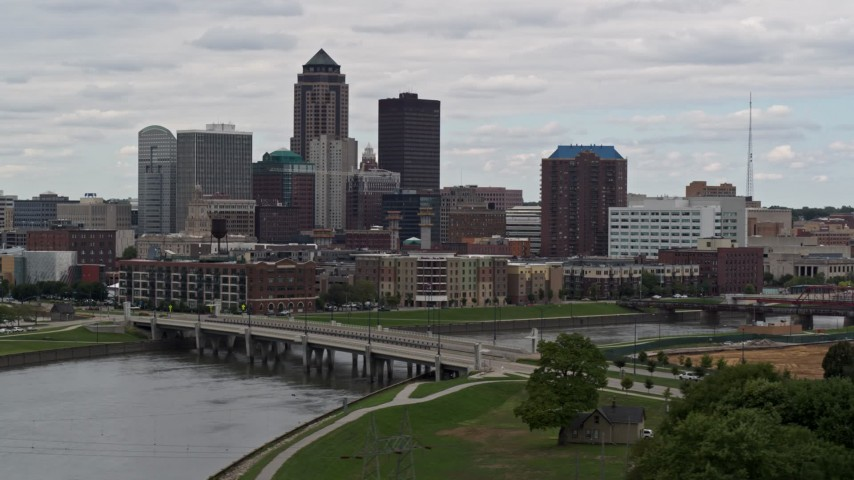 5.7K stock footage aerial video of passing by a Cedar River bridge with view of skyline, Downtown Des Moines, Iowa Aerial Stock Footage   DX0002_165_036