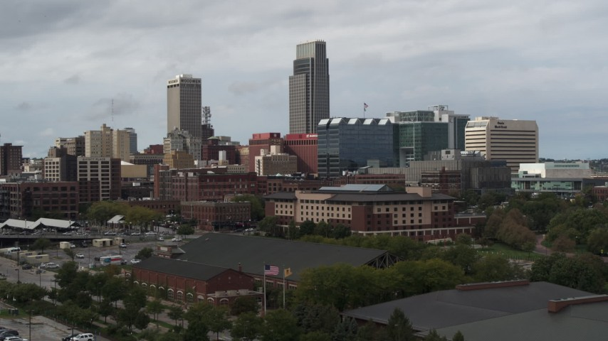 5.7K stock footage aerial video descend with view of a towering skyscraper and downtown skyline in Downtown Omaha, Nebraska Aerial Stock Footage | DX0002_168_013