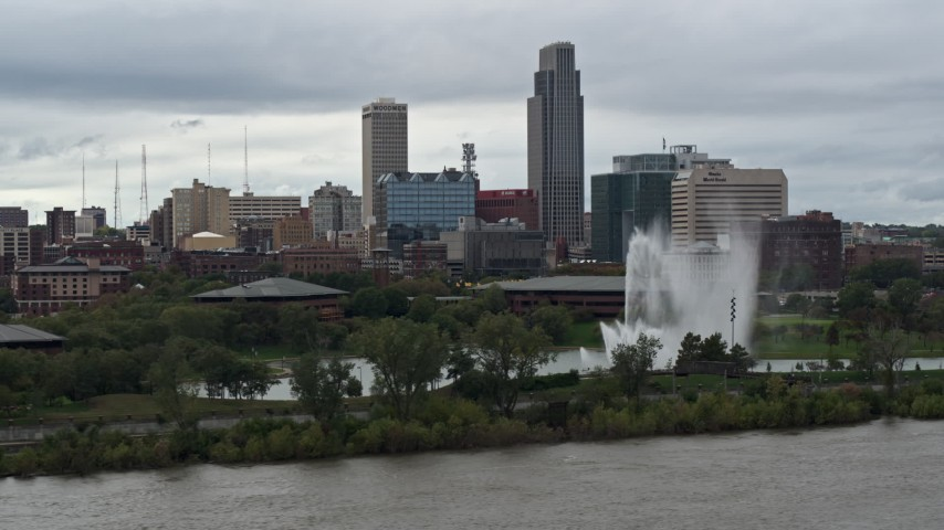 5.7K stock footage aerial video flying by a fountain and riverfront park with view of skyline, Downtown Omaha, Nebraska Aerial Stock Footage | DX0002_169_019