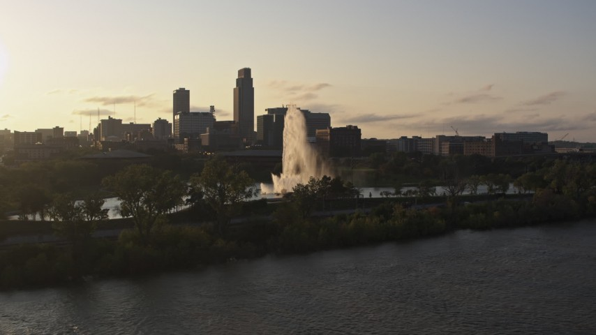 5.7K stock footage aerial video approach a fountain and riverfront park with view of skyline at sunset, Downtown Omaha, Nebraska Aerial Stock Footage | DX0002_172_006