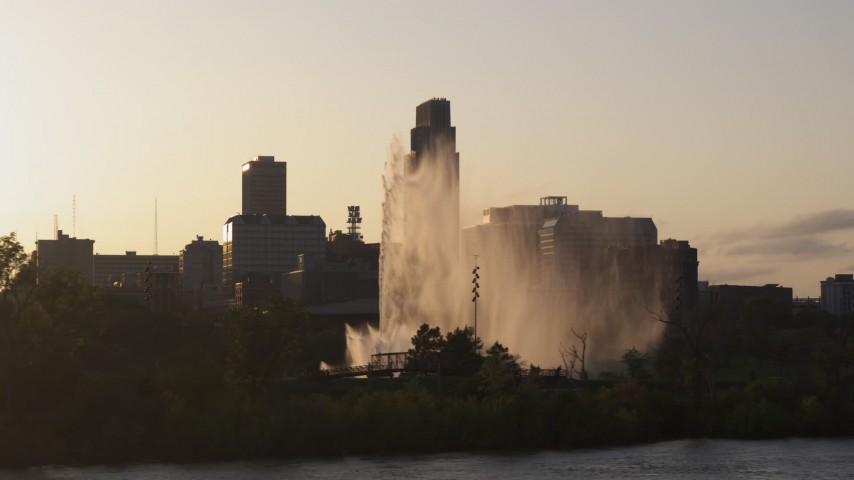 5.7K stock footage aerial video focus on skyscraper while flying by fountain at sunset, Downtown Omaha, Nebraska Aerial Stock Footage | DX0002_172_015