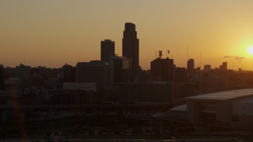 5.7K stock footage aerial video a reverse view of skyscraper and skyline with setting sun in background, Downtown Omaha, Nebraska Aerial Stock Footage | DX0002_172_024