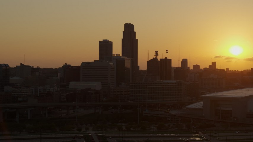 5.7K stock footage aerial video orbit skyscraper and skyline with setting sun in background, Downtown Omaha, Nebraska Aerial Stock Footage | DX0002_172_025