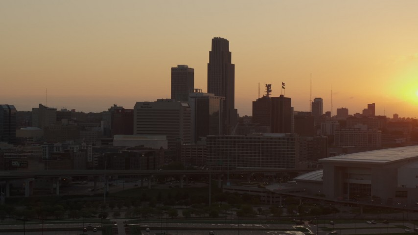 5.7K stock footage aerial video slowly fly away from and orbit skyscraper and skyline, setting sun in background, Downtown Omaha, Nebraska Aerial Stock Footage | DX0002_172_030
