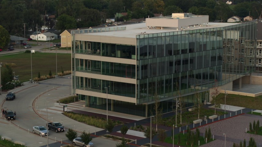 5.7K stock footage aerial video of a reverse view of a modern office building at sunset in Council Bluffs, Iowa Aerial Stock Footage | DX0002_172_035