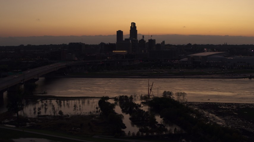 5.7K stock footage aerial video of the skyline seen from bridge over the river at twilight, Downtown Omaha, Nebraska Aerial Stock Footage | DX0002_172_042