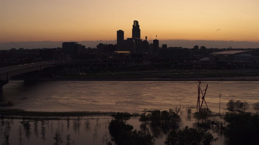 5.7K stock footage aerial video a view of the skyline while descending by the river at twilight, Downtown Omaha, Nebraska Aerial Stock Footage | DX0002_172_044