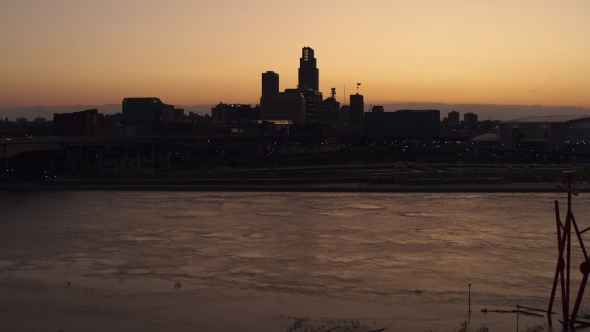 5.7K stock footage aerial video of ascending toward the skyline from the river at twilight, Downtown Omaha, Nebraska Aerial Stock Footage | DX0002_172_045