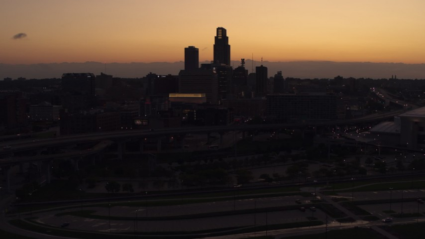 5.7K stock footage aerial video of flying away from the skyline at twilight, Downtown Omaha, Nebraska Aerial Stock Footage   DX0002_172_046