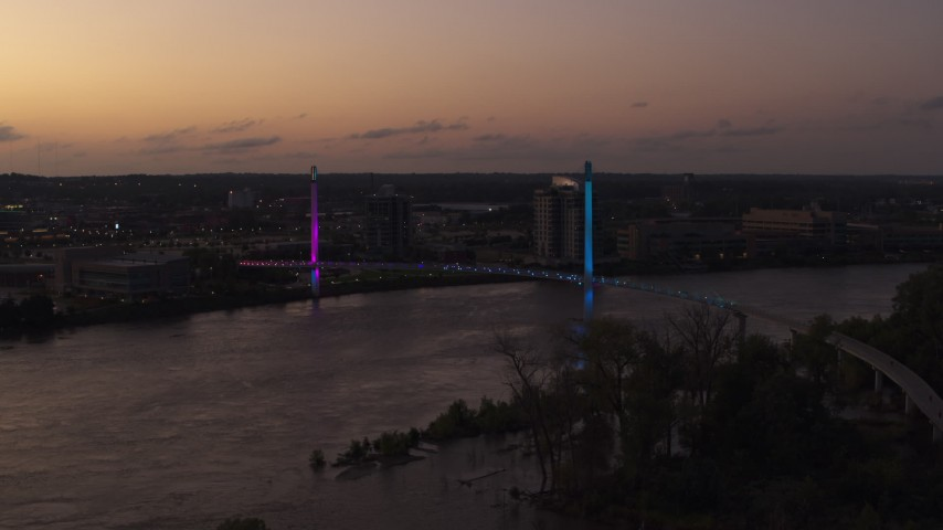 5.7K stock footage aerial video of passing a pedestrian bridge spanning the Missouri River at twilight, Omaha, Nebraska Aerial Stock Footage | DX0002_172_047