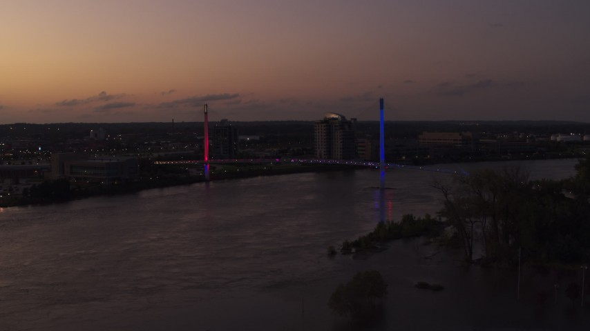 5.7K stock footage aerial video of flying away from a pedestrian bridge spanning the Missouri River at twilight, Omaha, Nebraska Aerial Stock Footage | DX0002_172_050