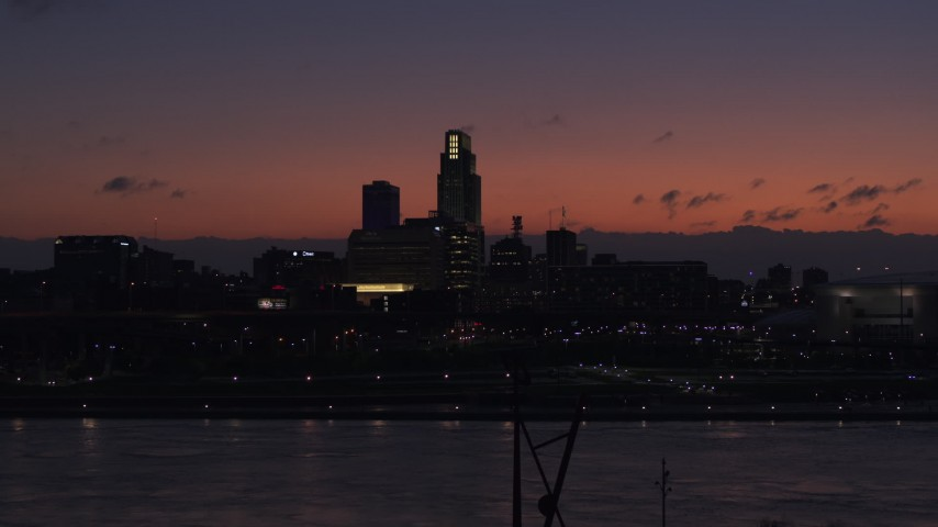 5.7K stock footage aerial video of ascending over the river toward the skyline at twilight, Downtown Omaha, Nebraska Aerial Stock Footage | DX0002_173_001