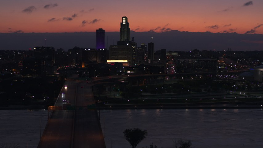 5.7K stock footage aerial video fly away from and by skyscrapers in the skyline at twilight, Downtown Omaha, Nebraska Aerial Stock Footage | DX0002_173_003