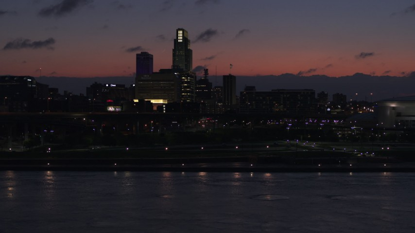 5.7K stock footage aerial video descend toward river while focused on the skyline at twilight, Downtown Omaha, Nebraska Aerial Stock Footage | DX0002_173_006