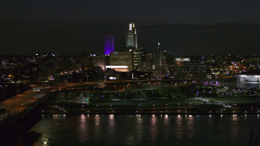 5.7K stock footage aerial video of the city's skyline at night, seen while flying over river, Downtown Omaha, Nebraska Aerial Stock Footage | DX0002_173_033