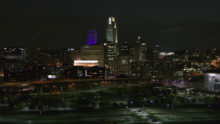 5.7K stock footage aerial video fly away from city's skyline at night, reveal the river, Downtown Omaha, Nebraska Aerial Stock Footage | DX0002_173_037