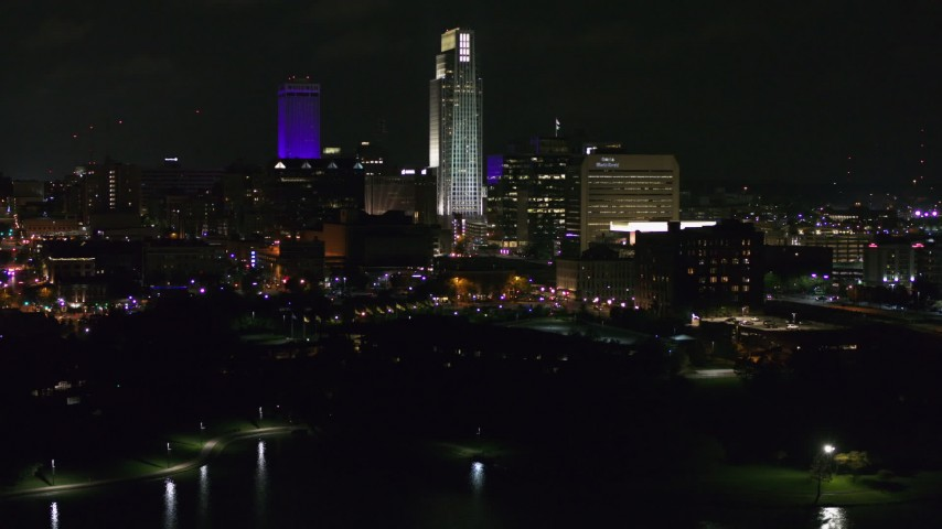 5.7K stock footage aerial video of slowly flying away from tall skyscrapers at night, Downtown Omaha, Nebraska Aerial Stock Footage | DX0002_173_049