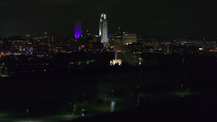 5.7K stock footage aerial video of tall skyscrapers behind the fountain lit up at night, Downtown Omaha, Nebraska Aerial Stock Footage | DX0002_173_052