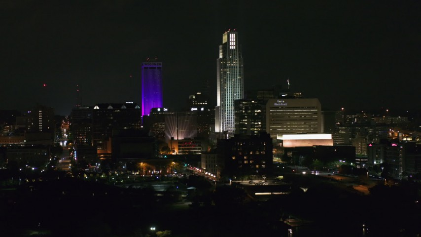 5.7K stock footage aerial video of focusing on towering skyscrapers at night, Downtown Omaha, Nebraska Aerial Stock Footage | DX0002_173_055