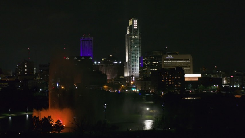 5.7K stock footage aerial video flying by skyscrapers and high-rises at night, reveal the park fountain, Downtown Omaha, Nebraska Aerial Stock Footage | DX0002_173_057