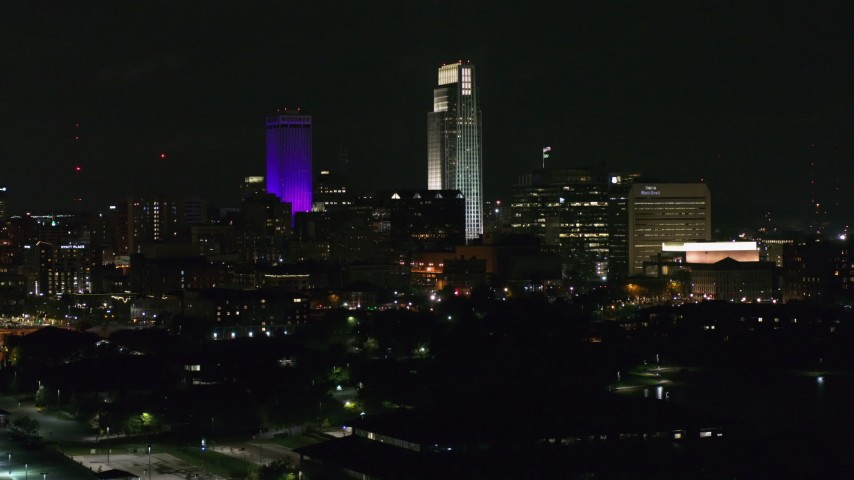 5.7K stock footage aerial video towering skyscrapers seen from the park at night, Downtown Omaha, Nebraska Aerial Stock Footage | DX0002_173_059