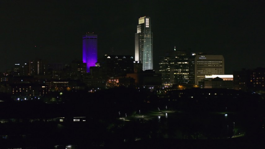 5.7K stock footage aerial video descending away from the city's skyscrapers seen from the park at night, Downtown Omaha, Nebraska Aerial Stock Footage | DX0002_173_061
