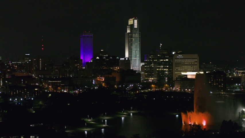 5.7K stock footage aerial video fly away from city's skyscrapers and the park fountain at night, Downtown Omaha, Nebraska Aerial Stock Footage | DX0002_173_064