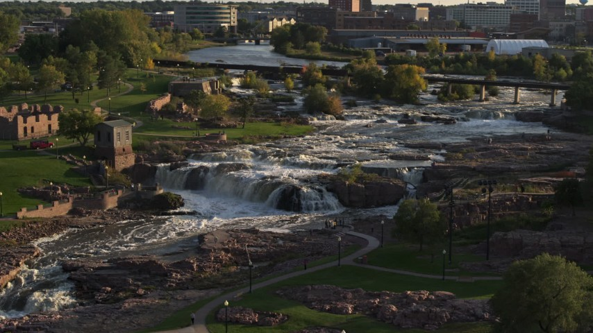 5.7K stock footage aerial video descending by the waterfalls at Falls Park at sunset in Sioux Falls, South Dakota Aerial Stock Footage | DX0002_176_007