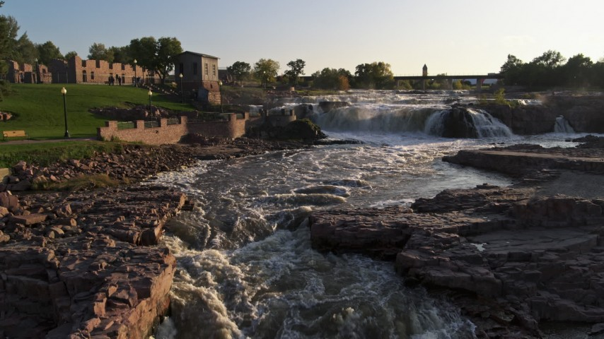 5.7K stock footage aerial video of low stationary view of waterfalls at sunset in Sioux Falls, South Dakota Aerial Stock Footage | DX0002_176_009