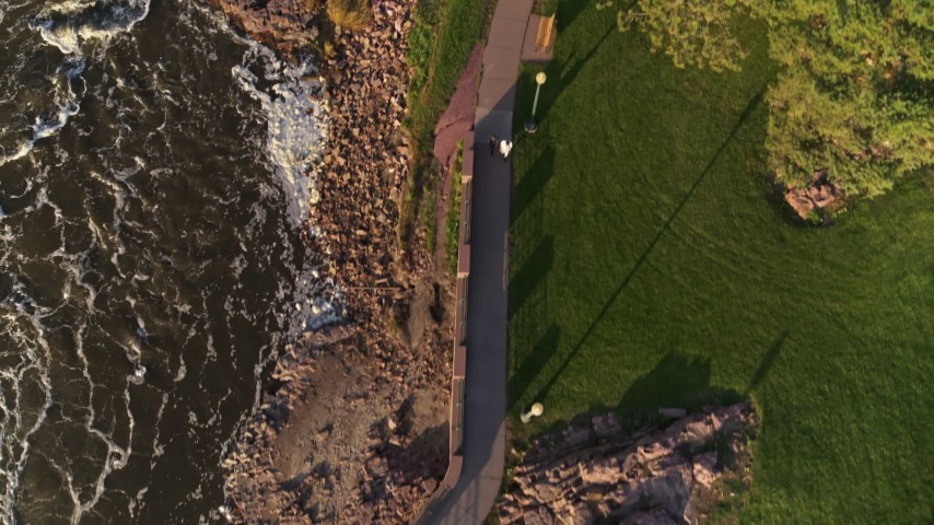 5.7K stock footage aerial video a bird's eye view of a path through the park by the river at sunset in Sioux Falls, South Dakota Aerial Stock Footage | DX0002_176_016