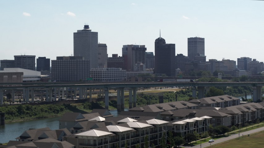 5.7K stock footage aerial video ascend from trees for view of the city's skyline and bridge in Downtown Memphis, Tennessee Aerial Stock Footage | DX0002_177_005
