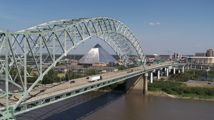 5.7K stock footage aerial video flying by cars crossing the bridge to Memphis, Tennessee, reveal Memphis Pyramid Aerial Stock Footage | DX0002_178_022