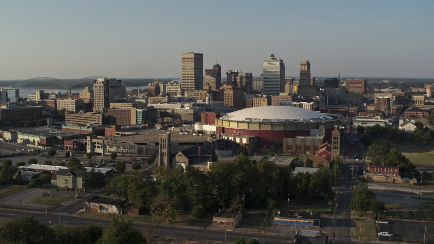 5.7K stock footage aerial video the city skyline and FedEx Forum arena at sunset during descent, Downtown Memphis, Tennessee Aerial Stock Footage | DX0002_180_031