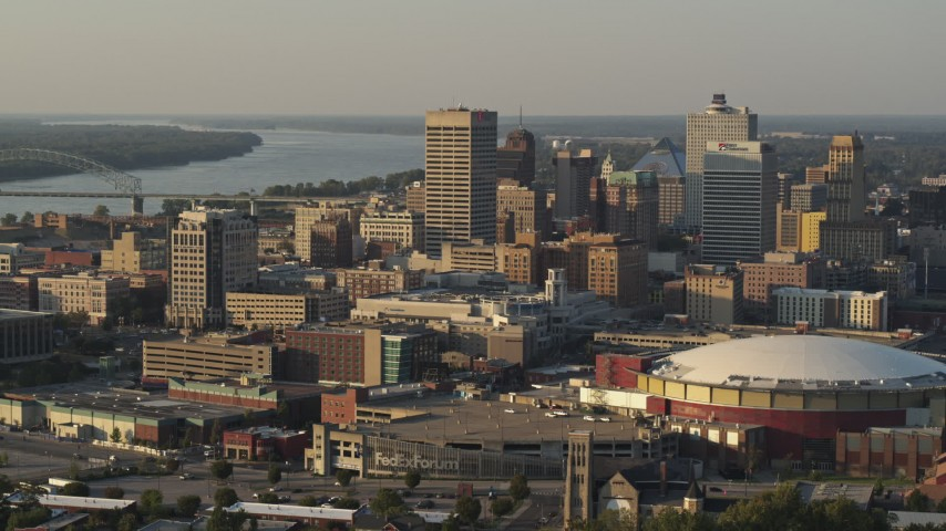 5.7K stock footage aerial video of a reverse view of tall office towers and the arena at sunset, Downtown Memphis, Tennessee Aerial Stock Footage | DX0002_181_006