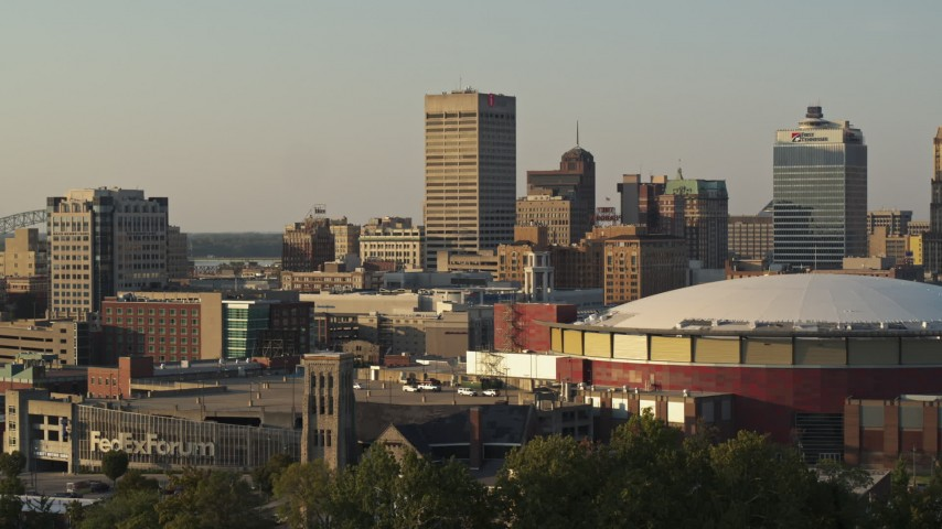 5.7K stock footage aerial video of One Commerce Square office tower at sunset, descend by arena, Downtown Memphis, Tennessee Aerial Stock Footage | DX0002_181_009
