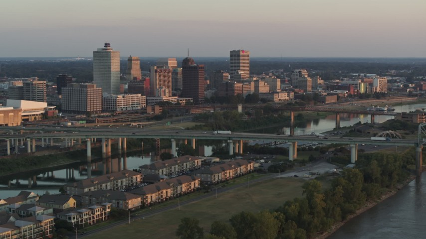 5.7K stock footage aerial video of the city's skyline behind the bridge and the river at sunset, Downtown Memphis, Tennessee Aerial Stock Footage | DX0002_181_010