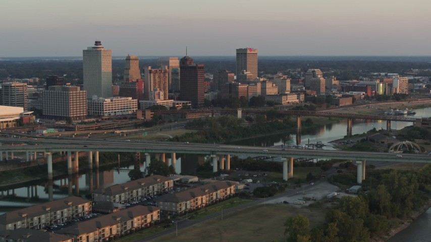 5.7K stock footage aerial video of flying by the city's skyline behind the bridge and the river at sunset, Downtown Memphis, Tennessee Aerial Stock Footage | DX0002_181_011