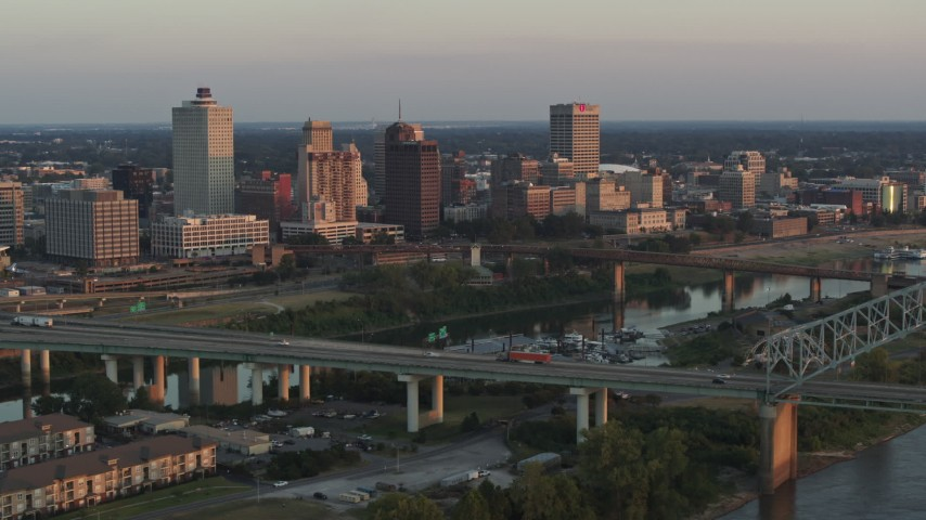 5.7K stock footage aerial video of passing the city's skyline behind the bridge and the river at sunset, Downtown Memphis, Tennessee Aerial Stock Footage | DX0002_181_012