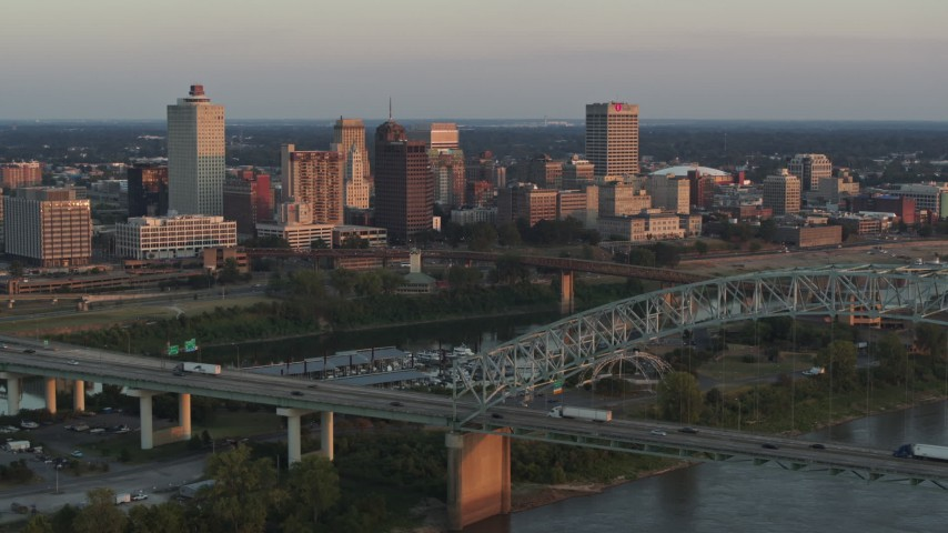 5.7K stock footage aerial video of a reverse view of the city's skyline behind the bridge and the river at sunset, Downtown Memphis, Tennessee Aerial Stock Footage | DX0002_181_013