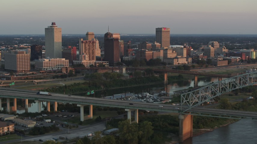 5.7K stock footage aerial video flyby the city's skyline behind the bridge and the river at sunset, Downtown Memphis, Tennessee Aerial Stock Footage | DX0002_181_014