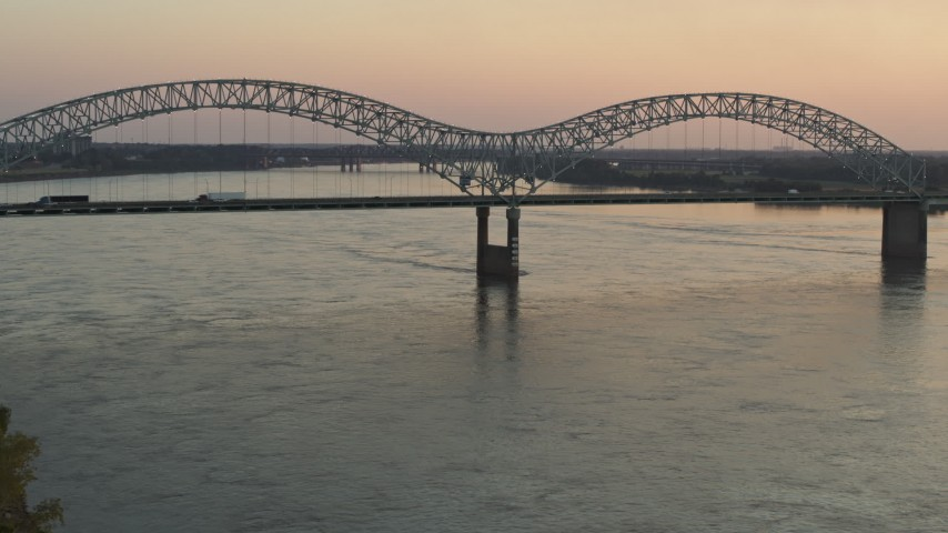 5.7K stock footage aerial video flying by traffic crossing the Hernando de Soto Bridge at sunset, Downtown Memphis, Tennessee Aerial Stock Footage | DX0002_181_017
