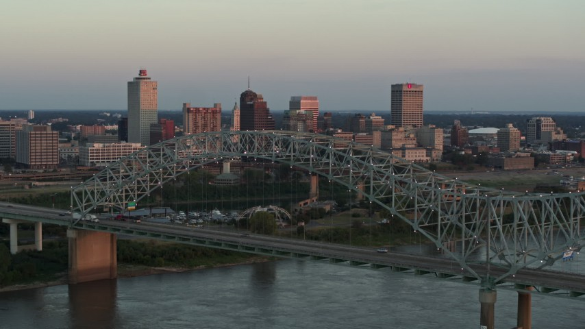 5.7K stock footage aerial video of ascending past the the bridge at sunset for a view of Downtown Memphis, Tennessee Aerial Stock Footage | DX0002_181_022