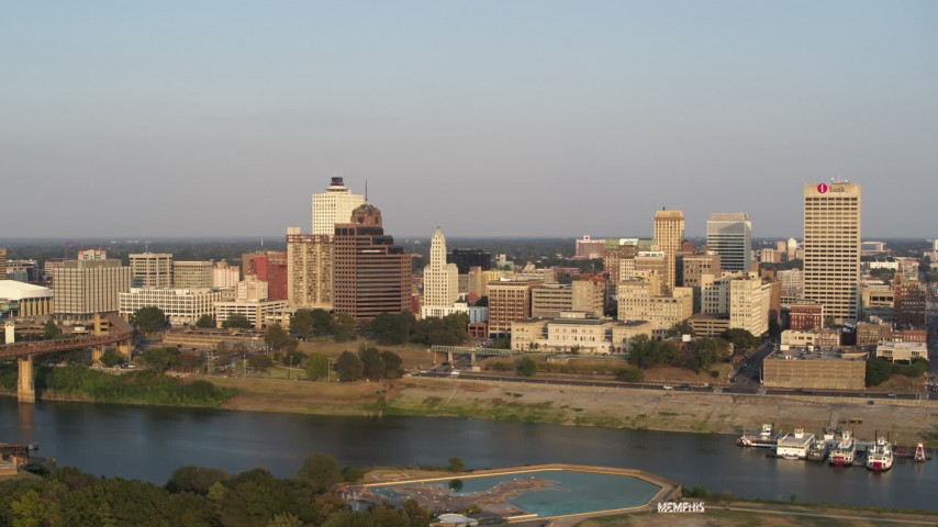 5.7K stock footage aerial video fly away from Raymond James Tower for wider view of skyline at sunset, Downtown Memphis, Tennessee Aerial Stock Footage | DX0002_186_010